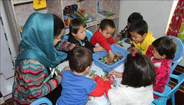 Afghan mothers study alongside their young children to improve their literacy